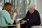 picture of psychologist  - Young female psychologist advising to older man - JPG