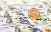 pic of one hundred dollar bill  - One american dollar coin lying on top of one hundred dollar bills close up - JPG