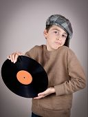 picture of newsboy  - Surprised and amazed cute young boy wearing a brown sweater and tartan newsboy cap holding and showing a vinyl record - JPG