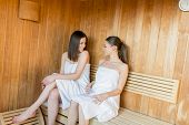 stock photo of sauna woman  - Young women relaxing on the bench in the sauna - JPG