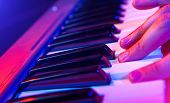 pic of soffit  - hands of musician playing keyboard in concert with shallow depth of field - JPG