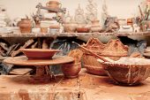 stock photo of molding clay  - Art of pottery. Still life of pottery making tools, brush and pottery wheel in clay studio