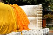 stock photo of big-foot  - Feet statue of Buddha looks out from under a yellow cloth - JPG