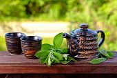 pic of peppermint  - Teapot with small cups and peppermint leaves - JPG