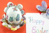 stock photo of decoupage  - Handmade decoupage Easter egg on a handmade paper plate with a Happy Easter card - JPG