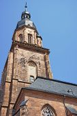 stock photo of holy-spirit  - Wall fragment clock tower and spire of Cathedral of Holy Spirit in Heidelberg at sunny weather - JPG