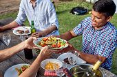 pic of gathering  - man passing dish healthy fresh salad at outdoor barbecue garden party gathering - JPG