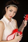 picture of ukulele  - Portrait teen girl playing ukulele no smile - JPG
