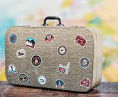 stock photo of cartographer  - old suitcase with stikkers on the floor against the backdrop of a world map - JPG