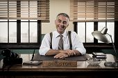 stock photo of 1950s  - Cheerful director sitting at office desk 1950s vintage office - JPG