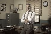 stock photo of 1950s style  - Confident smiling businessman with arms crossed 1950s style office - JPG
