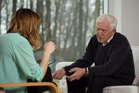 stock photo of older men  - Young female psychologist advising to older man - JPG