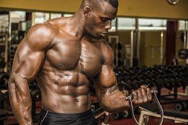 foto of bicep  - Hunky muscular black bodybuilder working out in gym exercising biceps on machine - JPG