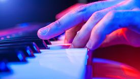 image of soffit  - hands of musician playing keyboard in concert with shallow depth of field - JPG
