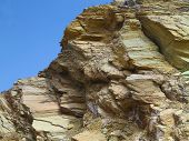picture of laminate  - Laminated structure of mountain rock over blue sky background - JPG