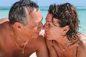 picture of crystal clear  - Couple nose against nose eye to eye loving couple on a beautiful deserted beach with turquoise and crystal clear waters of the Caribbean sea in the Dominican Republic on the island of Saonna - JPG
