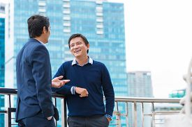 picture of coworkers  - Two Vietnamese male coworkers talking and smiling - JPG