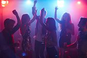 Happy students celebrating prom in night club, dancing with raised hands and holding glasses of cham poster