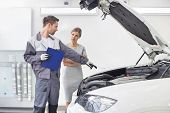 Young male repairman explaining car engine to female customer in automobile repair shop poster