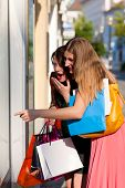 Two women being friends shopping downtown with colorful shopping bags, they are lolling into a glass