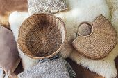 Empty wicker storage basket and handbag, blanket and cushions on sheep carpet, top view from above.  poster