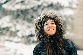 Winter girl in a fluffy hood in snowflakes. poster