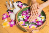 Woman Hands With A Bowl Of Aroma Spa Water Oil On Wooden Table poster