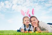 Easter bunny. Little girl with mother dressed as the Easter bunny lying on the grass with painted ea poster
