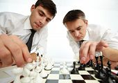 Two men looking at chess figures while making their move