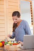 Junge Frau unter Rühren die Mahlzeit, die sie vorbereitet