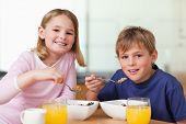 stock photo of orange-juice  - Children having breakfast in a kitchen - JPG