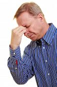 Elderly man with headache pinching back of his nose
