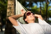 Tranquil Woman Relaxing Lying On A Hammock At Tropical Beach. Summer Vacation Relax And Tranquility  poster
