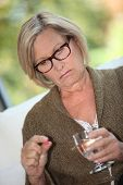 foto of ibuprofen  - Woman taking a pill with water - JPG