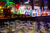 stock photo of night-club  - Glasses and assorted colorful bottles of alcoholic drinks in a night - JPG