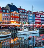 Sailboats Moored By Nyhavn Promenade Illuminated At The Evening, Copenhagen Old Town Cityscape, Denm poster