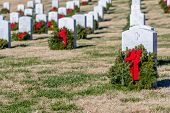 Veterans cemetery adorned with wreaths for the holiday season poster