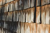 Side View Of Bright Brown Textured Old Wooden Tiles Wall. Atmospheric Background Of Sunny Dark And L poster