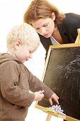 Boy drawing on a blackboard, teacher watching