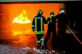 Firefighters Training For Fire Fighting In Germany. Firefighter In Fire Protection Suit Spraying Wat poster