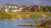 Scenic View With Homes Near Lake Against Mountain poster