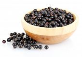 Black currant in wooden bowl isolated on white