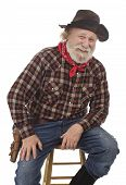 Cheerful Old Cowboy Sits On A Stool