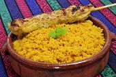 closeup of a plate with spiced couscous and a chicken skewer