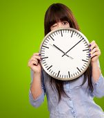 Woman Holding Clock Winking Isolated On Green Background