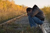 stock photo of sad man  - A man suffering from severe depression sitting on some train tracks - JPG