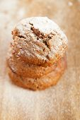 soft ginger cookies three stacked and dusted on wooden table, sieve with caster sugar on background,