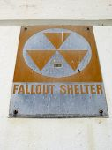 stock photo of cold-war  - Old Fallout Shelter Sign from the cold war era slowly rusts as it hangs on wall - JPG