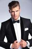 cutout picture of an elegant young fashion man holding both hands on his tuxedo jacket while looking