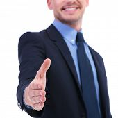 closeup on a young business man offering a hand shake with a smile on his face. focus on the hand. o